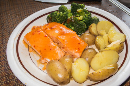 A plate of Salmon fillets, boiled potatoes and Broccoli