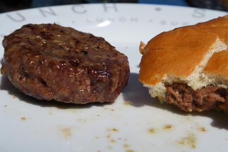 beefburger: Cooked Beefburger & a half eaten bun Stock Photo