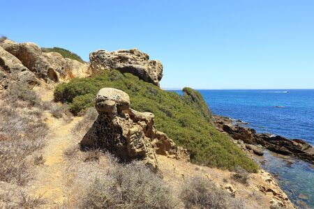 Rocks and green foliage overlooking the Atlantic ocean near Albufeira Stock Photo