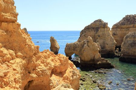 Rock formations and sea arches jutting out of the Atlantic coastline of Ponta Da Piedade in Lagos Stock Photo