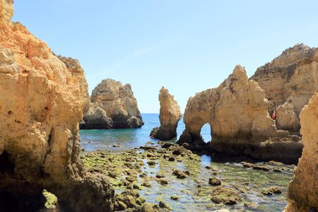 Rocky shoreline at Ponta Da Piedade surrounded by limestone cliffs