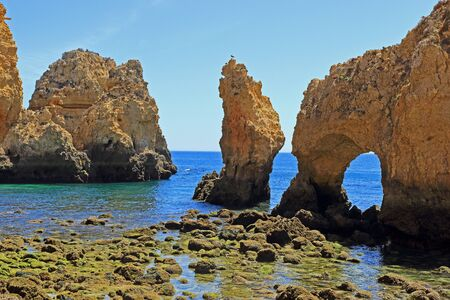 Coastal rock formations and sea arch at the Ponta Da Piedade Headland in Lagos
