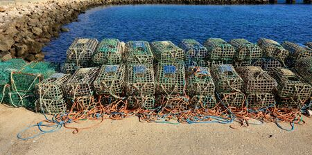 A row of lobster traps in the harbour wall at Rosso Do Veiga in Sagres