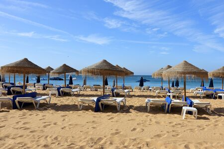 Straw umbrellas and deck chairs on the beach at Albufeira