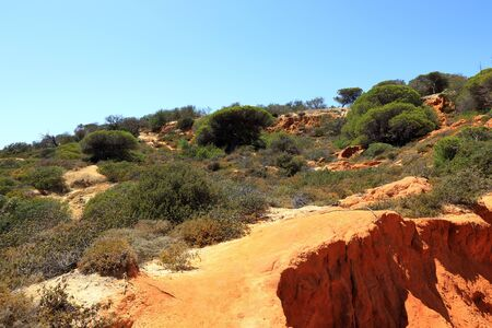 Red rocky pathways around Caminho Do Baleeira nature reserve near Albufeira Stock Photo