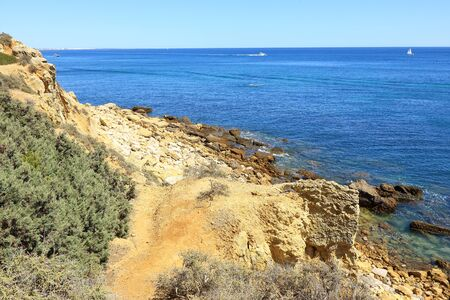 Dirt track leading down to the rocky coastline overlooking the Atlantic ocean near Albufeira