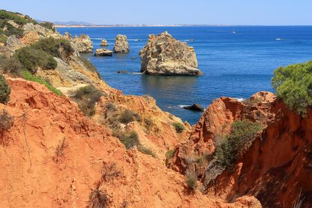 The red rocky and jagged coastline overlooking the Atlantic Ocean near Albufeira