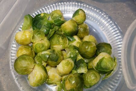 A plastic bowl full of Brussel Sprouts