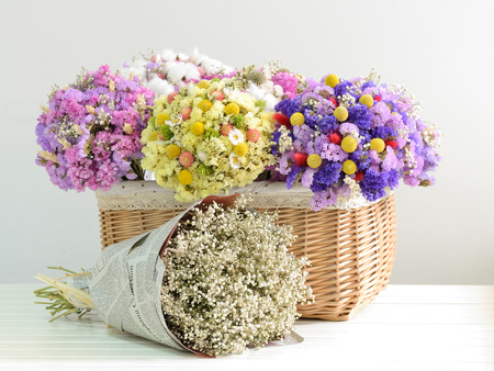 Multiple dried flowers tied with bouquets, put in the basket  Stock Photo