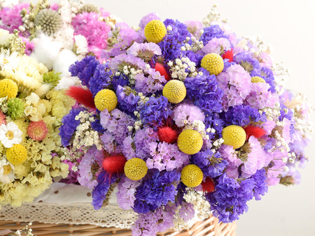 Multiple dried flowers tied with bouquets, put in the basket  photo