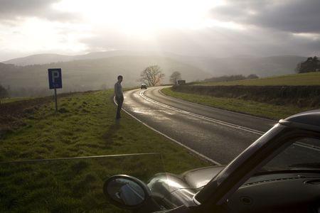 near side: a man on side of a road near a car
