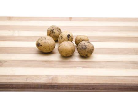 potatos: Brown Potatos on Wooden Plate Stock Photo