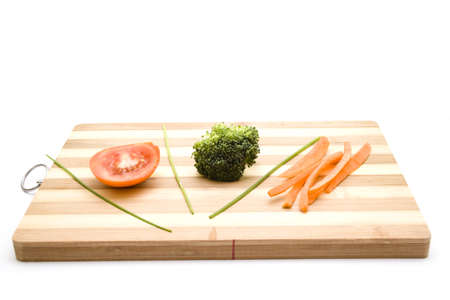 Tomato with Broccoli and Carrots on Wooden Plate