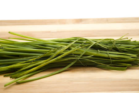 Fresh Chives on wooden plate