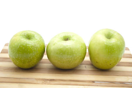 Green Apples on wooden plate