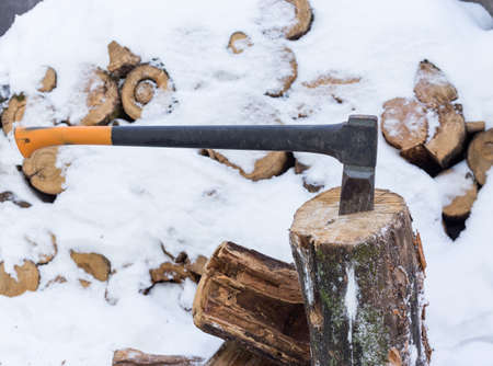 The ax stuck in a tree stump on a background of chopped firewood stored in the winter Stock Photo