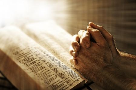 mano de dios: orando sobre una biblia Foto de archivo