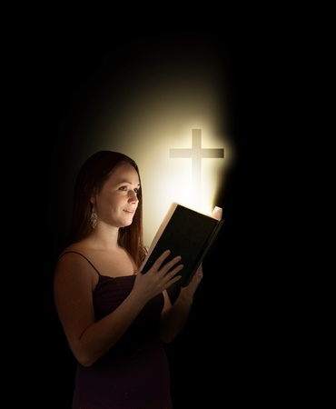 A woman reading an open bible with a cross coming out.