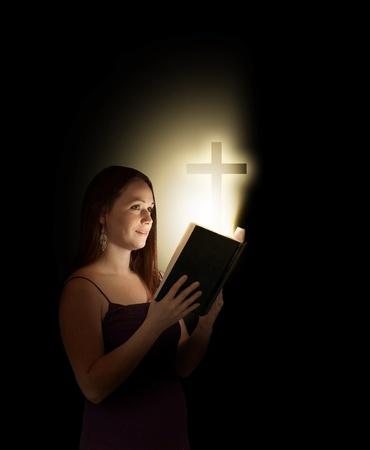 mujer arrodillada: Una mujer que lee una Biblia abierta con una cruz que sale.