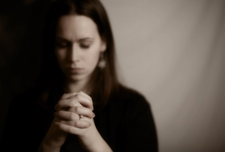 kneeling woman: A brunette woman praying with her hands together
