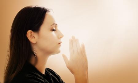 arrodillarse: Una mujer rezando con las manos juntas sobre fondo blanco