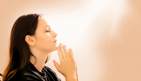 A woman praying with light beams coming down photo