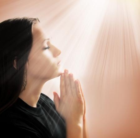 Woman praying with lights shining down Stock Photo