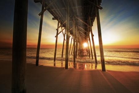 Sunrise on the beach near the pier Imagens