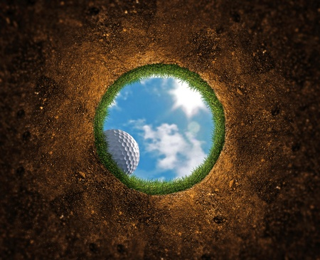near: Golf ball falling over the edge into the hole Stock Photo
