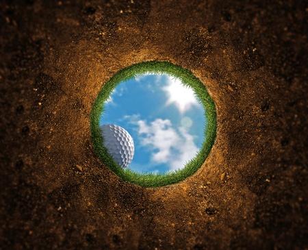 poblíž: Golfový míček padá přes okraj do otvoru Reklamní fotografie