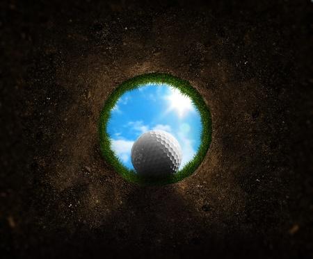 Golfbal vallen in de beker van unieke perspectief Stockfoto