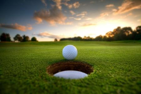 balle de golf: Une balle de golf sur le point de tomber dans la tasse au coucher du soleil