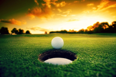 caddie: Golf ball about to fall into the cup at sunset Stock Photo