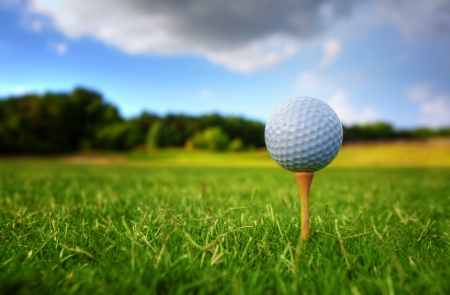 Golf ball on tee with bright green grass on summer day