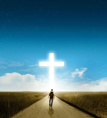 jesus on cross: Un hombre que camina hacia una gran cruz cristiana que brilla intensamente