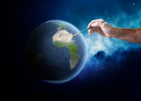 Ein Künstler malt die Erde mit einem Pinsel.