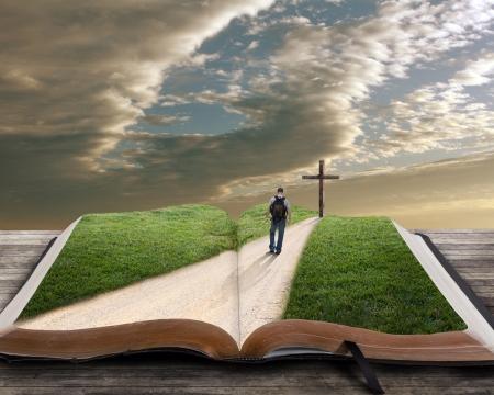 Een open bijbel met gras en een man lopen naar een kruis