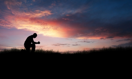 kneeling: Man kneeling down in a field to pray Stock Photo