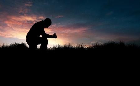 arrodillarse: El hombre orando en el campo de hierba Foto de archivo