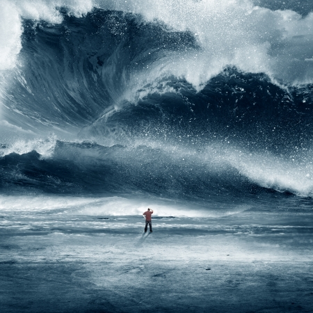 Huge Tidal wave crashing onto the beach with man Stock Photo