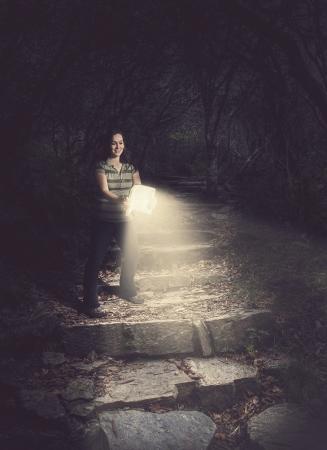 taschenlampe: Frau, die eine gl�hende Bibel in den Wald.