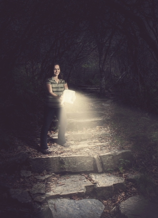 flashlights: Woman holding a glowing Bible in the forest.
