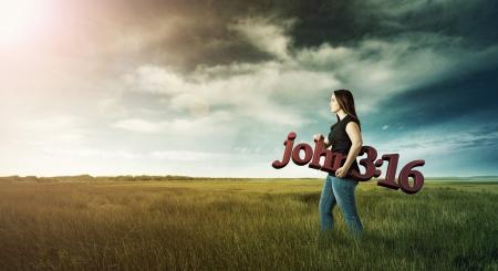 john: Woman carrying a Bible verse through the field  Stock Photo