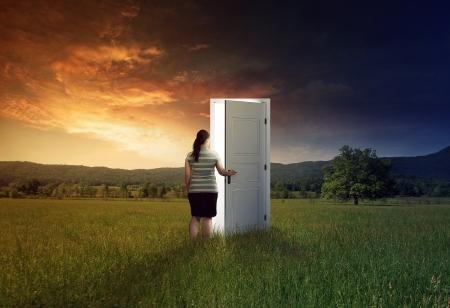 abriendo puerta: Mujer que camina a través de una puerta en el campo