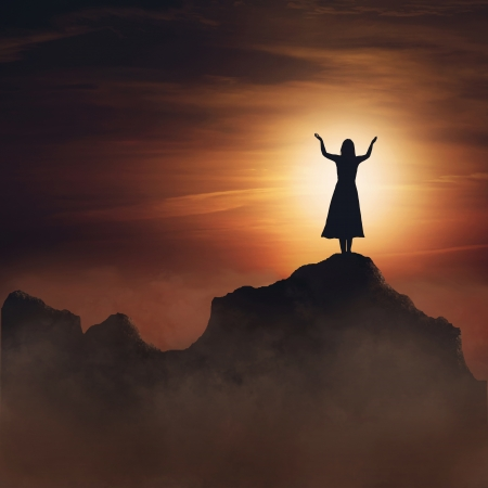 Woman on mountain in praise and worship.
