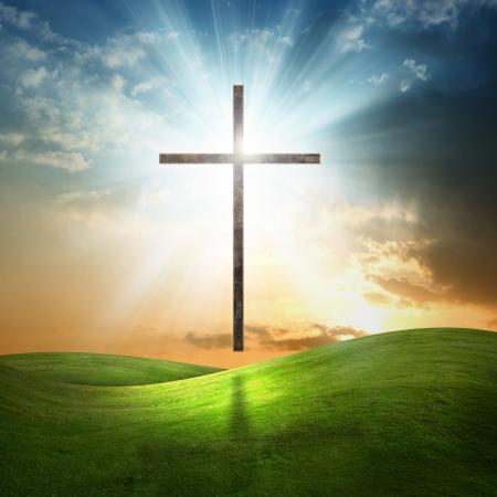 gospel: Christian cross above grass field at sunset.