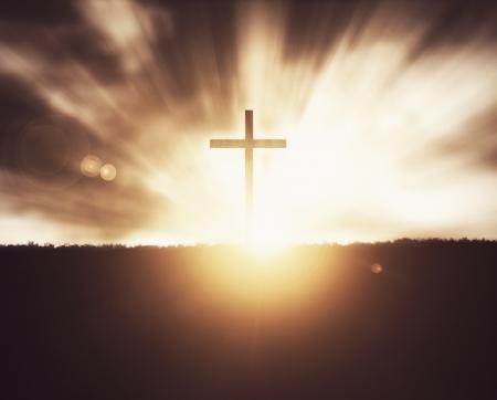 Cruz cristiana en la puesta del sol en fondo del campo de hierba.