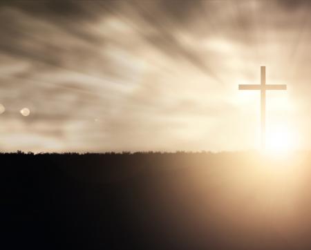 almighty: Una croce cristiana al tramonto con riflessi di luce. Archivio Fotografico