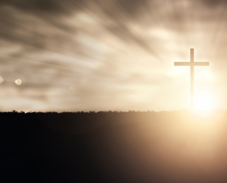 cruz cristiana: Una cruz cristiana en la puesta del sol con destellos de luz.