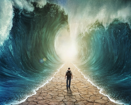 A man walking through the water with the waves parted. photo